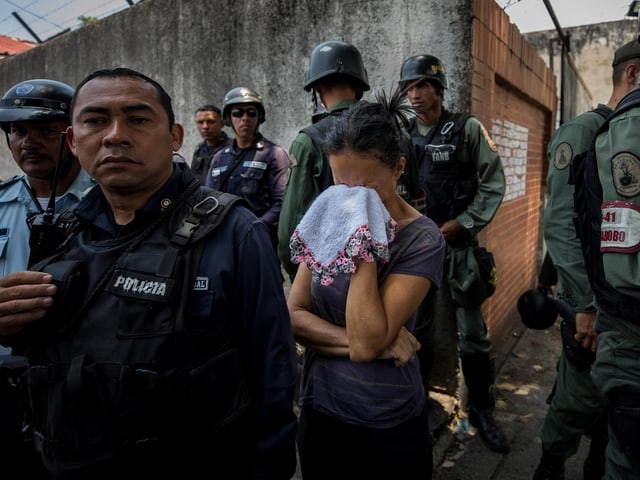 Frau weint zwischen Polizisten.