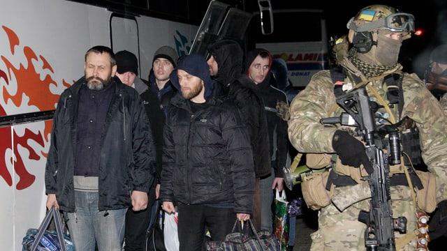Ein ukrainischer Soldat begleitet eine Gruppe gefangener Separatisten, die jetzt freigelassen werden.