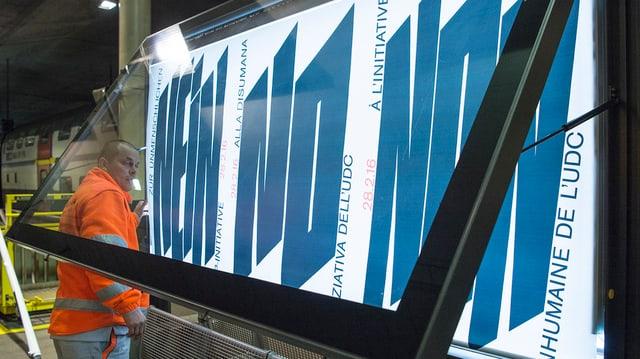 Plakatarbeiter montiert Abstimmungsplakat gegen DSI