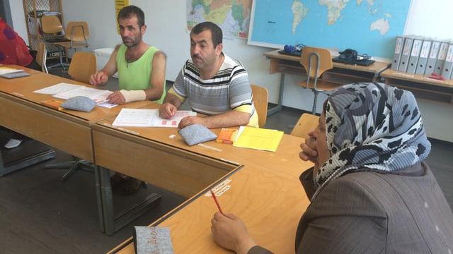 Drei Flüchtlinge in einem Klassenzimmer.