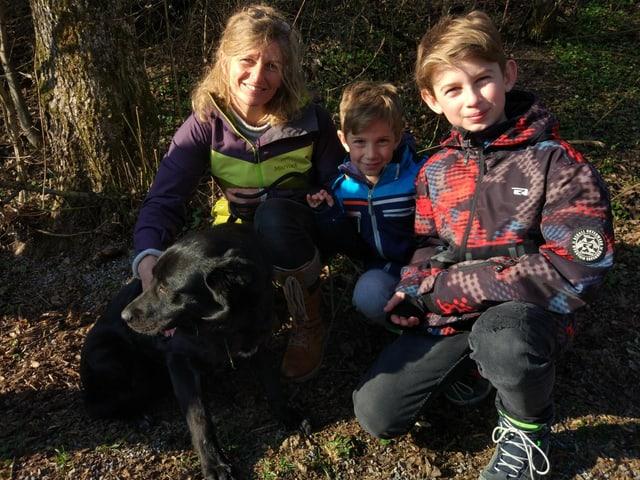 Eine Frau mit zwei kleinen Buben und einem schwarzen Hund.