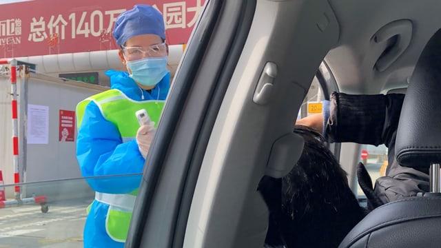 Person in Schutzanzug misst Temperatur.