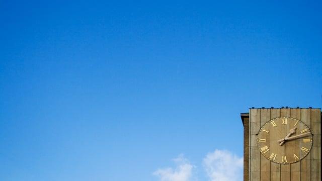 Ein Ziffernblatt ragt in den blauen Himmel.