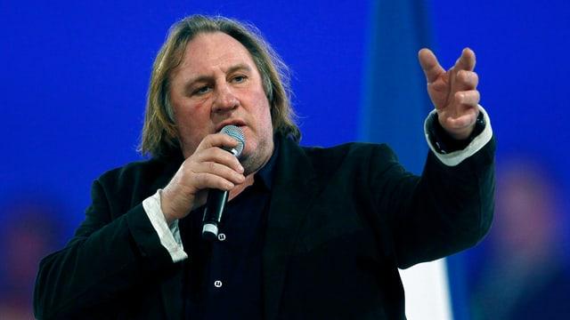 Depardieu mit Mikrofon in der Hand hält eine Rede.