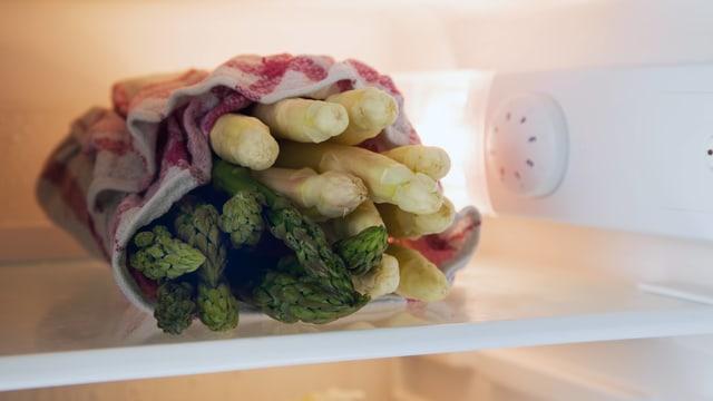 Grüner und weisser Spargel in einem Tuch im Kühlschrank.