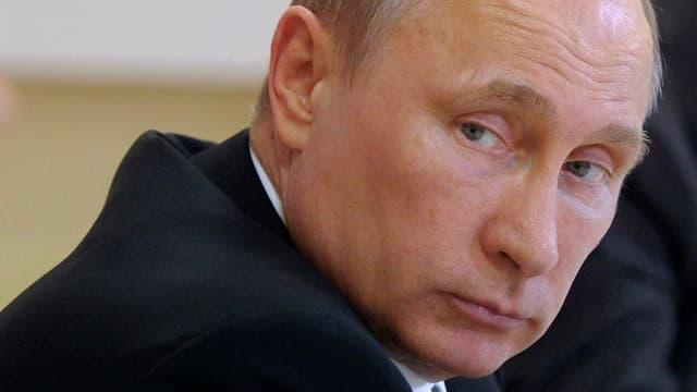 Präsident Wladimir Putin im schwarzen Sako, der an der Kamera vorbeiblickt.