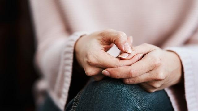 Frau mit rosa Pullover verschränkt die Hände
