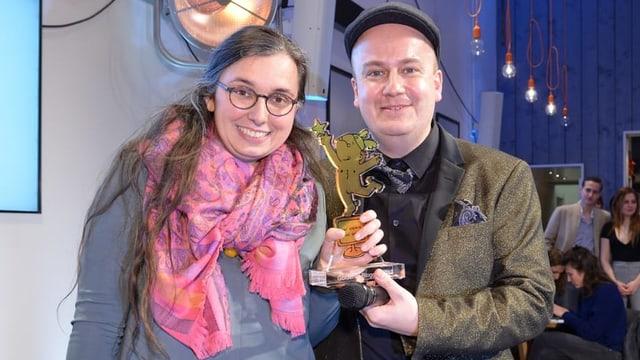 Ein Mann übergibt einer jungen Frau mit Brille eine Statue.