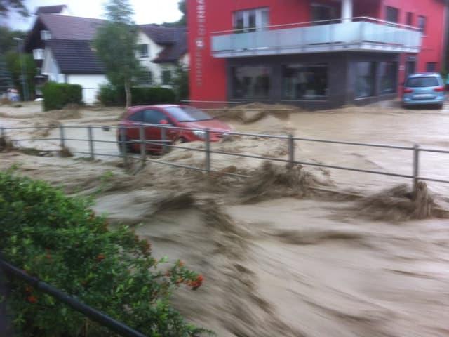 Ein Auto fährt auf einer überfluteten Strasse