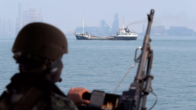 Symbolbild: Ein Soldat mit Helm und Gewehr schaut aufs Meer und einen Öltanker.