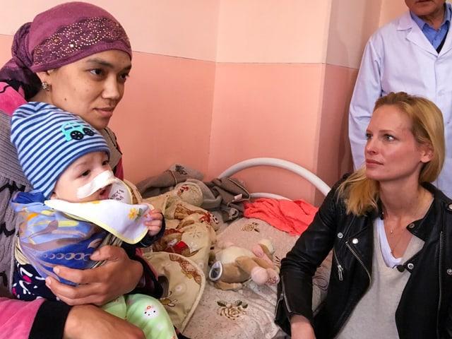 Sarina Arnold kniet vor dem Spitalbett. Darauf sitzen Mutter mit kleinem Abdulla auf dem Schoss. Er hat ein grosses Pflaster auf der Nase. Der Arzt beobachtet die ganze Situation.