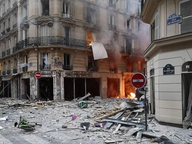 Trümmerübersähte Strasse und ein Feuer mit Rauch rechts im Hintergrund.