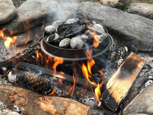 Eine Gusseisenpfanne steht auf der Glut eines Feuers.