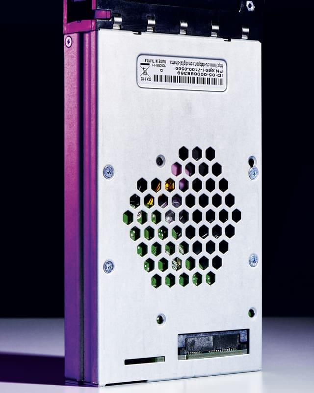 Eine graue Festplatte, einseitig leicht violett angestrahlt.