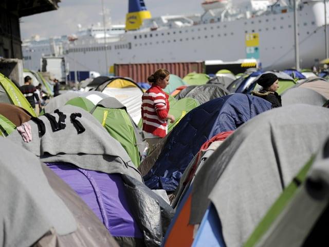 Dutzende Zelte, dazwischen halten sich Frauen auf, im Hintergrund eine Passagierfähre.