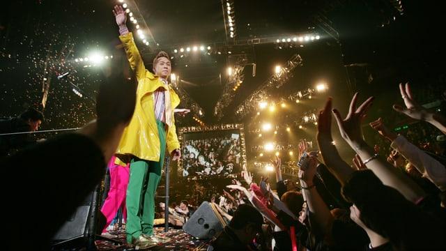 Ein Mann auf einer Bühne winkt in die Menge.