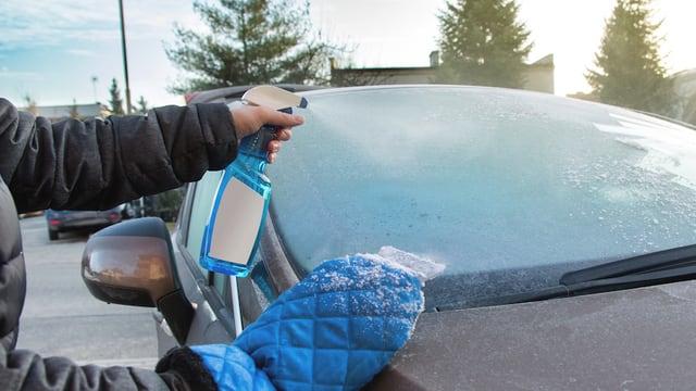 Autofahrer bearbeitet gefrorene Scheibe mit Enteiserspray und Eiskratzer.