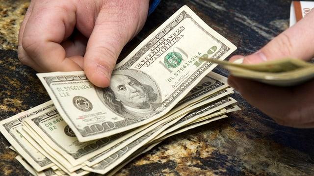 Hundert-Dollar-Noten werden auf einen Tisch abgezählt.