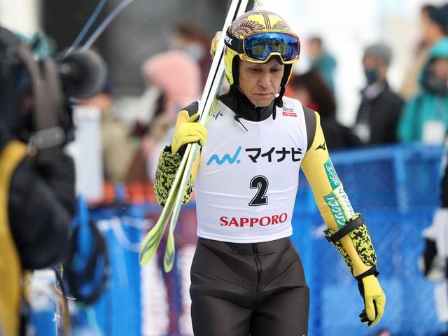 Noriaki Kasai trägt die Ski