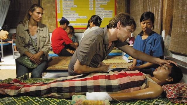 Ein Mann pflegt einen asiatischen Bub in einem Krankenhaus.