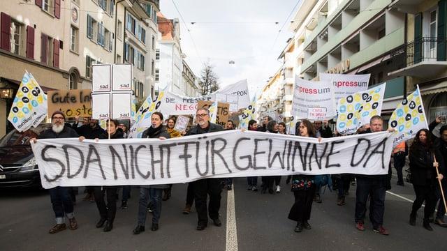 Mitarbeiter der SDA protestieren mit Transparenten auf der Strasse