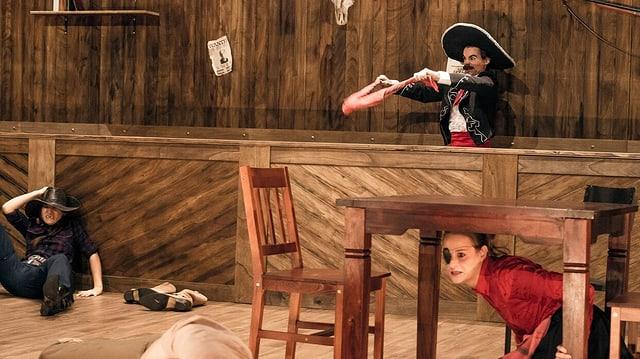 Drei Schauspieler in einem Westernsaloon. Einer sitzt am Boden, eine Frau unter einem Tisch und ein Mann hinter der Bar.