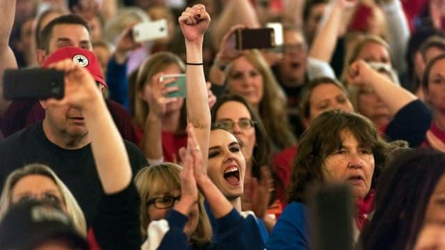 Menschen stehen in einer Menge, eine junge Frau reckt den Arm hoch und macht eine Faust, den Mund zu einem Ausruf geöffnet.