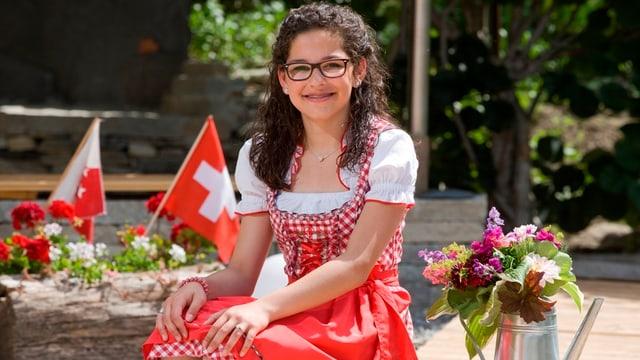 Walker im rot-weissen Dirndl sitzend auf einer Veranda im Hintergrund Schweizer Fähnli.