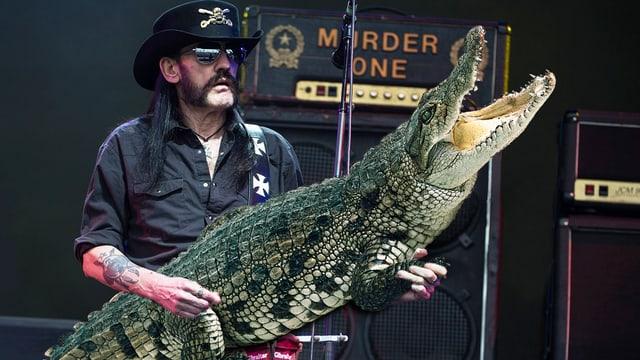 Lemmy Kilmister hält anstatt eine Gitarre ein Krokodil in der Hand.