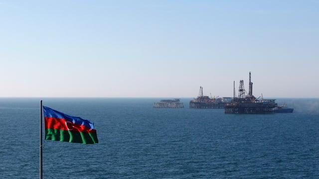 Ein Flagge von Aserbaidschan weht vor einer Ölplattform im Kaspischen Meer.