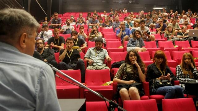 Junge Menschen in einem Kinosaal, vorne auf der Bühne spricht Sokurov ins Mikrofon