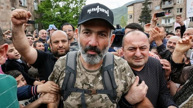 Paschinjan mit Tarn-T-Shirt und schwarzer Baseball-Cap inmitten von Demonstranten, die ihm unter die Arme greifen.