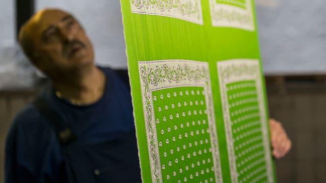 Ein Mann inspiziert frisch produzierte Glarner Tüechli.