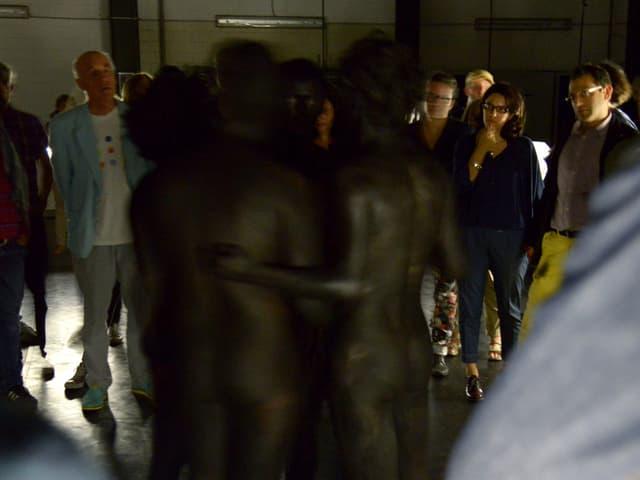 Schwarz angemalte Tänzer stehen in der Mitte des Raumes.