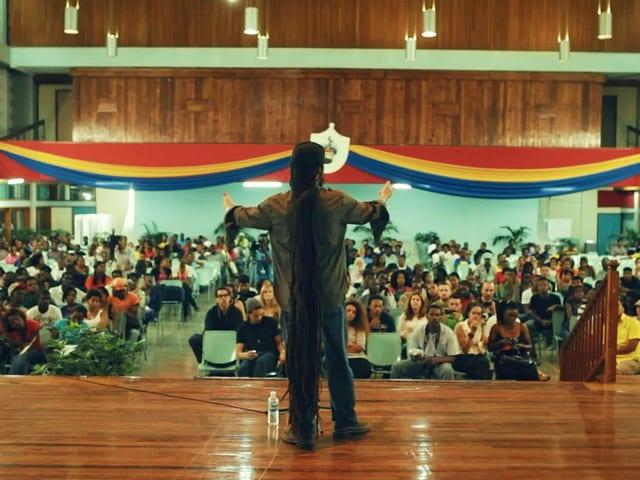 Man sieht Damian Marley vor einer Schulklasse.