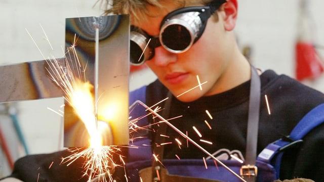 Junger Mann mit dicker Schutzbrille schweisst ein Stück Metall, Funken sprühen.