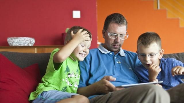 Vater sitzt mit seinen Söhnen auf dem Sofa und schauf auf ein Tablet