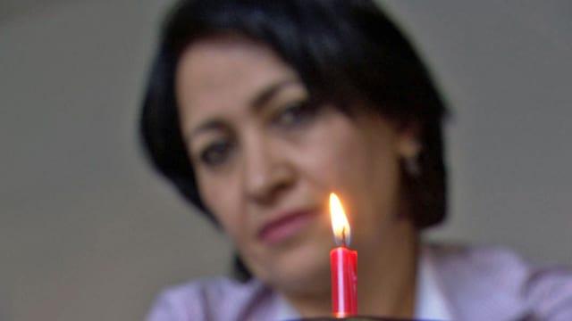 Eine Frau betrachtet eine Geburtstagskerze.