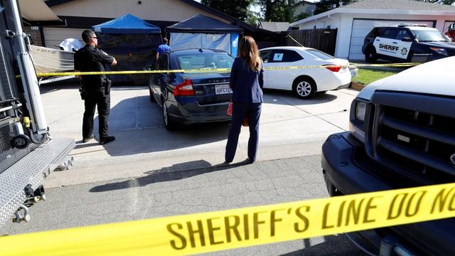 Absperrpand, Polizisten vor einem Haus stehend