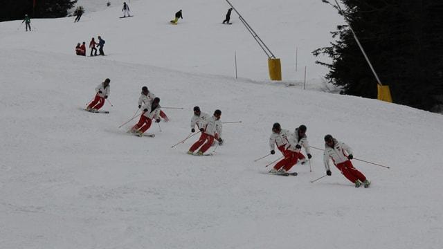 8 skiunz en colonna in davos l'auter che fan stortas curtas sin pista.