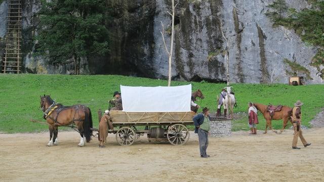 Theaterszene im Freien mit Pferden und Planwagen.