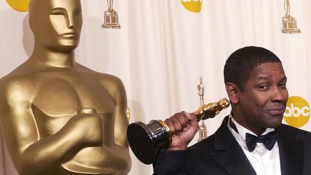 Denzel Washington hält den Oscar in der Hand.