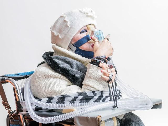Eine ältere Frau atmet durch eine Maske, an die ein Schlauch angeschlossen ist.