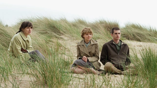 Zwei Frauen und ein Mann sitzen an einem Strand. Eine Frau sitzt leicht abseits.