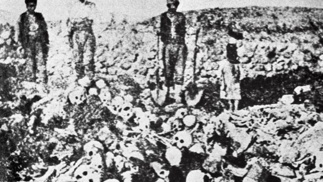 Männer vor Bergen von Skeletten.