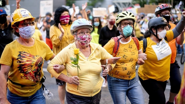 In Portland stellte sich am Montag auch eine Mauer aus Müttern (Wall of Moms) schützend vor die Demonstrierenden. Sie wollen verhindern, dass ihre Söhne von den mit massiver Gewalt operierenden Spezialeinheiten des Bundes verletzt werden.