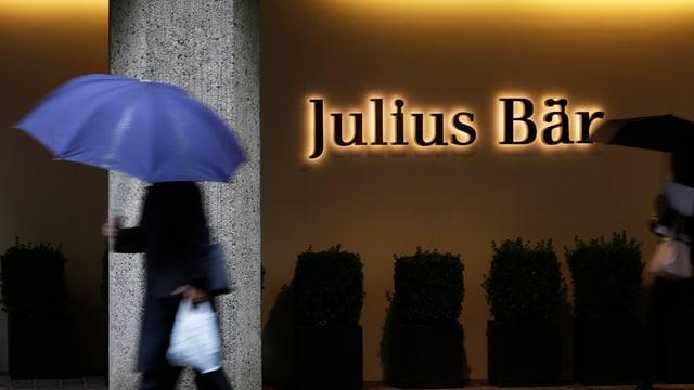 Mann mit Regenschirm vor Julius Bär-Logo