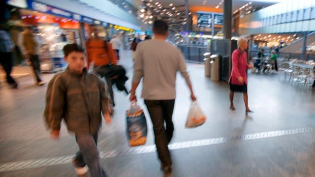 Leute mit Einkaufstaschen in Bahnhofshalle
