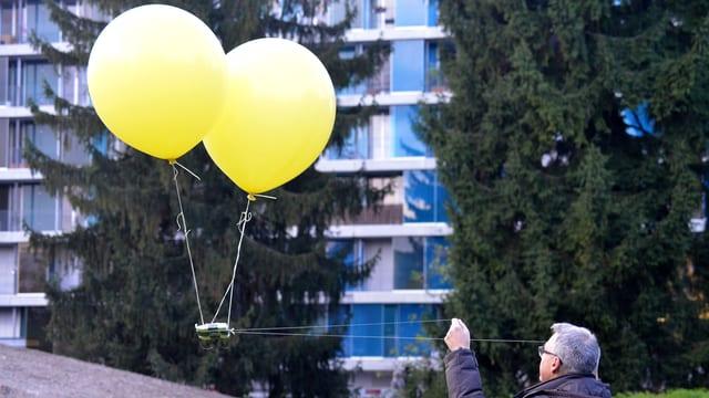 Das Bild zeigt Digitalredaktor Peter Buchmann, der mit zwei Schnüren zwei Luftballone steuert, unter denen eine Kamera befestigt ist.