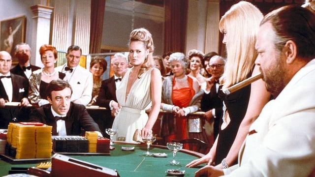 Ursula Andress, Orson Welles, Peter Sellers an einem Pokertisch.